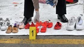 Lực lượng cứu hộ sắp xếp lại các đôi giầy của nạn nhân được tìm thấy. Ảnh: Getty