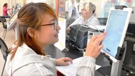 Người dân đánh giá thái độ phục vụ của cán bộ tại UBND quận Bình Thạnh. Ảnh: VIỆT DŨNG