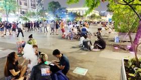 Người trẻ vô tư ngồi bệt ở phố đi bộ Nguyễn Huệ (quận 1) để ăn uống và xả rác
