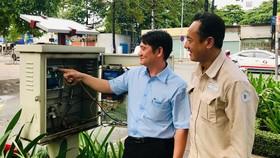 Anh Phan Trường Phát (trái) hướng dẫn đồng nghiệp  cách vận hành tủ năng lượng mặt trời
