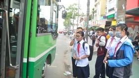 Học sinh đón xe buýt. Ảnh: THÀNH TRÍ