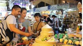 Du khách nước ngoài đang chọn mua các mặt hàng thủ công mỹ nghệ, quà lưu niệm tại chợ Bến Thành   Ảnh: Gia Hân