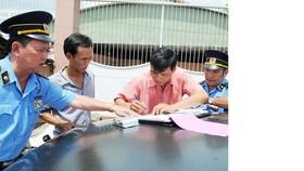 Tài xế ký biên bản vi phạm luật giao thông tại cửa ngõ phía Đông thành phố          Ảnh: CAO THĂNG
