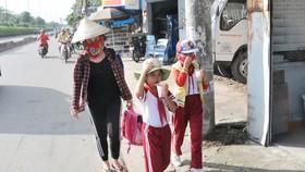 Học sinh một trường tiểu học ở huyện Hóc Môn trên đường về nhà sau giờ tan trường. Ảnh: THÀNH TRÍ