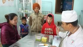 Quân y của Trạm quân dân y kết hợp Thoọng Pẹ đang thăm khám cho trẻ em trong bản và hướng dẫn cho các bậc phụ huynh các phòng tránh bệnh cho con em. Ảnh: Báo Hà Tĩnh
