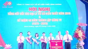 Ông Nguyễn Hoàng Thao (bìa trái), Phó Bí thư Thường trực Tỉnh ủy và ông Đặng Minh Hưng (bìa phải), Phó Chủ tịch UBND tỉnh trao Cờ thi đua của Thủ tướng Chính phủ cho Công ty TNHH MTV Xổ số kiến thiết Bình Dương