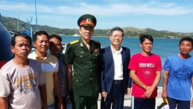 Vietnamese Ambassador to the Philippines Ly Quoc Tuan (third from right) and Defence Attache Nguyen Van Hung (centre) with five fishermen who return home after a ceremony on November 29 (Photo: VNA)