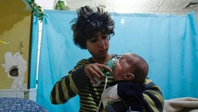 A Syrian boy holds an oxygen mask over an infant's face at a makeshift hospital in Eastern Ghouta, where three reported chlorine attacks have occurred in recent weeks. - AFP/VNA Photo