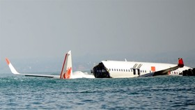 A Lion Air Boeing 737 lies submerged in the water after missing the runaway during landing at Bali's international airport near Denpasar on April 14, 2013. Local authorities confirmed that flight JT610 departed the airport near the capital Jakarta on sche
