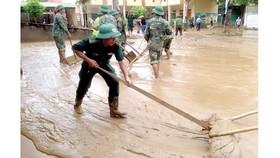 Bộ đội Biên phòng tỉnh Nghệ An giúp dân dựng lại nhà, dọn dẹp trường lớp. Ảnh: DUY CƯỜNG
