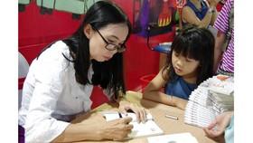 Nhà văn Võ Diệu Thanh ký tặng sách cho độc giả tại Hội sách TP Cần Thơ lần thứ 2. Ảnh: VĂN THÀNH LÊ