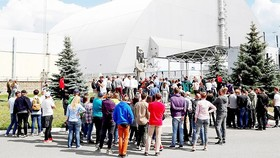 Du khách đứng bên ngoài mái vòm kim loại bảo vệ lò phản ứng thứ tư của Chernobyl