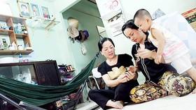 Ba thế hệ trong gia đình liệt sĩ Trần Đông Sơ lần giở những kỷ vật của anh. Ảnh: MAI HOA
