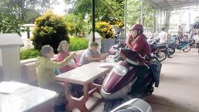 Người dân ngao ngán ngồi chờ trước cửa trụ sở Công an xã Thới Tam Thôn để xác nhận hồ sơ cá nhân