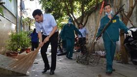 Lãnh đạo quận 7 tham gia dọn vệ sinh cùng người dân. Ảnh: VIỆT DŨNG