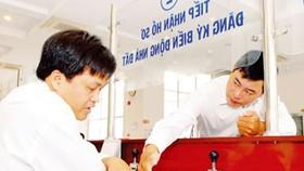 Nhân viên Văn phòng đăng ký quyền sử dụng đất Sở Tài nguyên - Môi trường TPHCM hướng dẫn người dân làm hồ sơ nhà đất