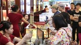 Khách hàng giao dịch vàng miếng tại Bảo Tín Minh Châu. (Ảnh: Đức Duy/Vietnam+)