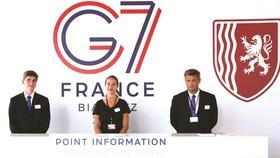 在法國比亞里茨,工作人員在新聞中心迎接媒體記者。