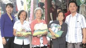 富山五行廟慈善組組長鄒國榮(右一)與第十五坊祖國陣線委員會主席阮玉錦(左一)向貧困長者贈送禮物。