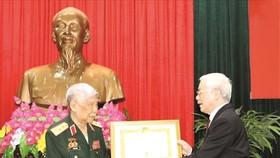 總書記、國家主席阮富仲向黎可漂同志頒授紀念章。