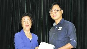 市越南祖國陣線委員會副主席、市各少數民族文學藝術協會主席劉金華頒發獎學金給碩士畢業生楊元昌。