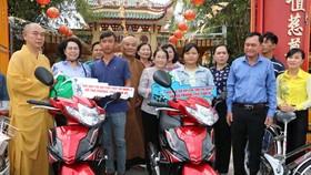 本市領導與釋慧功上座向2戶華人家庭贈送摩托車。