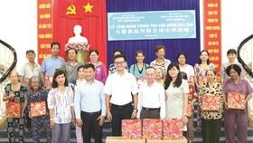 黃副總經理與本報領導向華人贈送月餅。