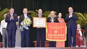 Các đồng chí Tất Thành Cang và Nguyễn Thành Phong trao danh hiệu Anh hùng lực lượng vũ trang nhân dân. Ảnh: VIỆT DŨNG