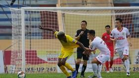Hậu vệ Nam Định cố gắng ngăn chặn Oliveira trước khung thành nhà. Ảnh: MINH HOÀNG