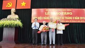 Đồng chí Trần Lưu Quang chúc mừng các đồng chí nhận Huy hiệu 70 năm tuổi Đảng