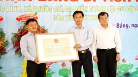 Chủ tịch UBND tỉnh Tây Ninh Phạm Văn Tân (bìa phải)  trao bằng công nhận di tích lịch sử chi bộ Đảng đầu tiên của tỉnh