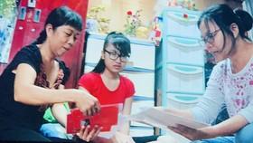 Em Lâm Huế Bình (giữa) được Hội Bảo vệ quyền trẻ em TPHCM  tặng sách vở, động viên đến trường