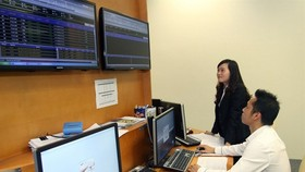 Specialists monitor a bidding session on the Hanoi Stock Exchange. (Photo: VNA)