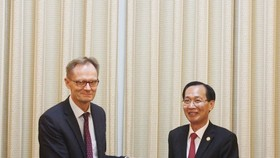 Standing Vice Chairman of the municipal People's Committee Le Thanh Liem (R) and his Finnish guest. (Photo: hcmcpv.org.vn)