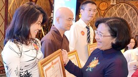 Ms.Than Thi Thu, Head of the Department of Propaganda & Education of HCMC Party Committee (R ) offers certificates of merit to individuals and organizations at the ceremony. (Photo: Sggp)