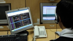 An underwriter monitors stock trades at the Hanoi Stock Exchange (Photo: VNA)