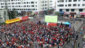 Fans gather outdoor to watch a football match (Photo: VNA)