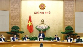 Prime Minister Nguyen Xuan Phuc (standing) speaks at the regular government meeting (Photo: VNA)