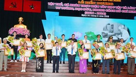 Secretary of HCM City Party Committee Nguyen Thien Nhan and chairman of the municipal People's Committee Nguyen Thanh Phong present certificates of merit to honored individuals and units. (Photo: Sggp)