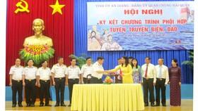 Đại diện Tỉnh ủy An Giang và Quân chủng Hải quân trao văn bản ký kết hợp tác tuyên truyền biển, đảo. Ảnh: NHƯ NGUYỄN