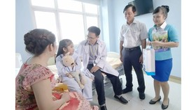 Social workers visit a kid patient to encourage her to overcome the illness (Photo: SGGP)