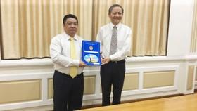 Phó Chủ tịch UBND TPHCM  Lê Văn Khoa trao quyết định cho ông Võ Khánh Hưng (phía bên trái).