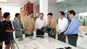 Đồng chí Nguyễn Thiện Nhân và đồng chí Lê Thanh Liêm đang xem một số sản phẩm Công ty Cổ phần Công nghiệp hỗ trợ Minh Nguyên sản xuất cho tập đoàn Samsung