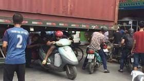 Bất chấp nguy hiểm, người dân chui gầm container để lưu thông