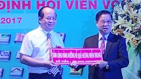 Viện sĩ, GS-TS Hoàng Quang Thuận (áo trắng) trao 100 triệu đồng cho Chủ tịch Câu lạc bộ ủng hộ đồng bào bị thiệt hại do cơn bão số 10 gây ra.