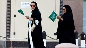 Phụ nữ cầm quốc kỳ Saudi Arabia mừng Quốc khánh ở Riyadh. Ảnh: REUTERS