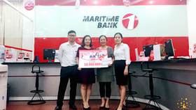 """Chị Nguyễn Thị Phượng (thứ hai từ phải sang) đã may mắn nhận được sổ tiết kiệm Maritime Bank 50 triệu đồng đầu tiên của chương trình """"Chọn Maritime Bank hôm nay, ngàn ưu đãi mỗi ngày""""."""