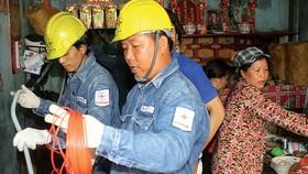 Nhân viên điện lực sửa chữa, thay thế thiết bị điện hư hỏng cho hộ gia đình nghèo tại quận 6 Ảnh: Nguyễn Hưng