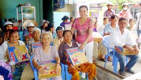 Bà Tâm (đứng) trao quà tặng người nghèo