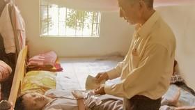 Đại diện UBND xã Thủy Bằng trao tiền bạn đọc Báo SGGP hỗ trợ anh Nguyễn Văn Hiếu